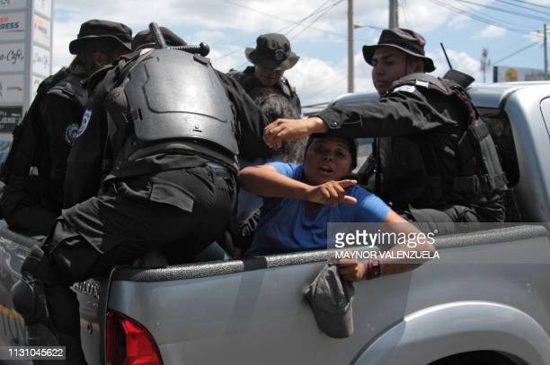 Nicaraguan riot police officers leave with two people arrested while their were heading to a demonstration called by opposition groups to demand the...