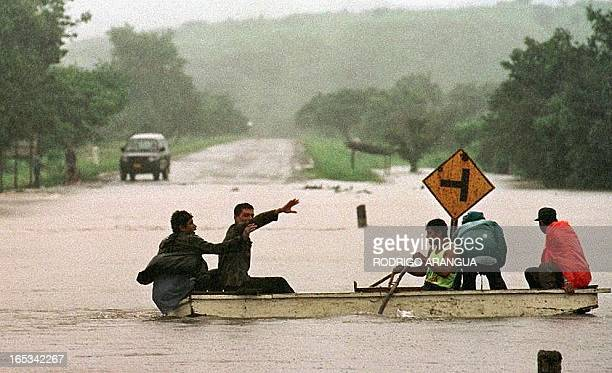 Nicaraguan volunteers cross a flooded Pan American Highway near Las Playitas 75 kms north of Managua looking for stranded people Officials report...