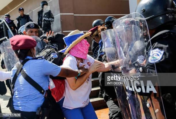 Nicaraguan woman is arrested by riot police during a protest against the government of President Daniel Ortega in Managua on October 14 2018