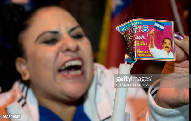 A Nicaraguan woman living in Costa Rica burns her identification card of the Sandinista National Liberation Front during a demonstration against the...