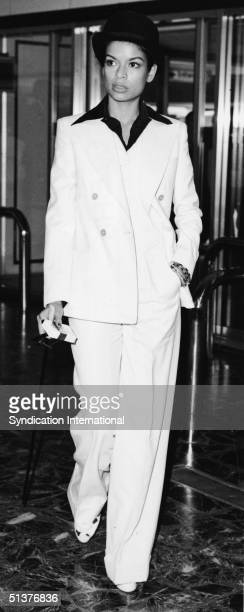 Nicaraguanborn actress Bianca Jagger dressed in a white threepiece suit and black bowler hat walks through Heathrow Airport with a cane pack of...
