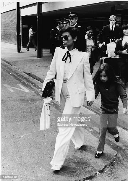 Nicaraguan-born model Bianca Jagger wears a double-brested white suit as she and her daughter Jade walk across the street in front of a group of...