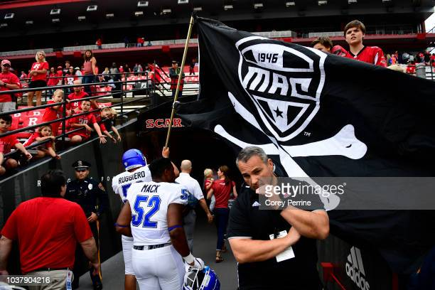 Nicco Ruggiero of the Buffalo Bulls waves the MAC Conference flag after the game against the Rutgers Scarlet Knights at HighPoint.com Stadium on...