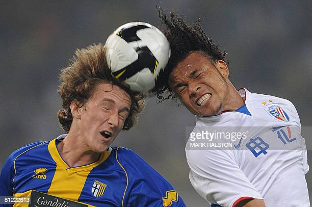 Niccolo Galli from the Italian team Parma heads the ball against Wang Dalei of the Chinese Super League club Shanghai Shenhua during their Fiat Cup...