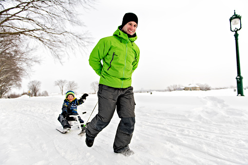 A nice Father drag his boy in sled 1080325354