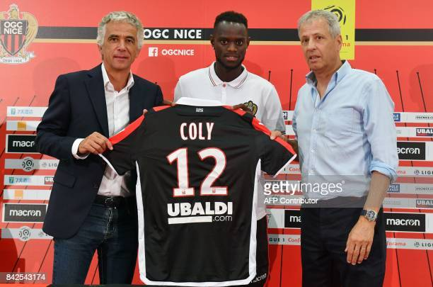 OGC Nice football club's new recruit Senegalese defender Racine Coly poses with his new jersey between Swiss head coach Lucien Favre and French...
