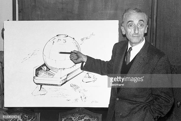 4/13/1964 Nice France Pointing to a rendering of his Spheric Submarine Base design Jacques Cousteau explains how five men will spend the night...