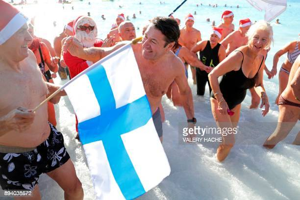 Nice mayor Christian Estrosi greets a man waving the Finnish flag as he takes part in the traditional Christmas bath on December 17 2017 in the...