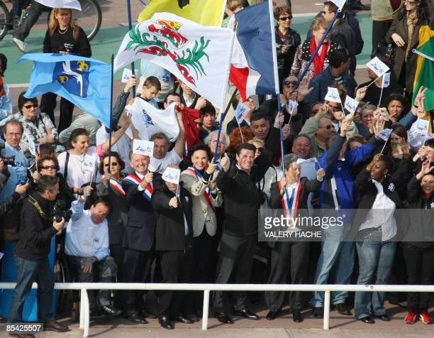 Nice' mayor Christian Estrosi waves flags along with other people in Nice on The French Riviera on March 14 2009 to show support to Nice's candidacy...
