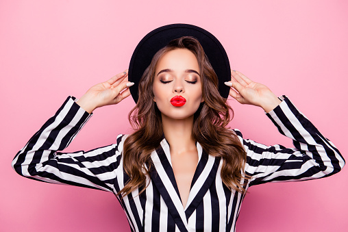 Nice, rich, independent, confident, successful, luxury, sexy girl holding hat on her head with hands, having closed eyes, blowing kiss to the camera, isolated on pink background 964839486