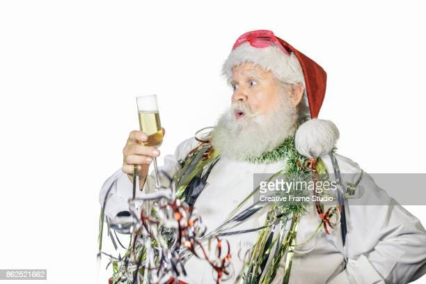Nice Santa Claus celebrating and dancing  with a glass of champagne and party favors