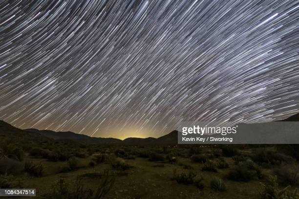 nice star trails over desert landscape in a higher elevation section of anza-borrego desert state park in san diego county, california usa. foreground contains a few patches of glow from occasional traffic on a nearby highway. - julian california stock photos and pictures