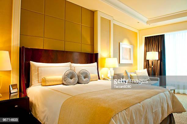 A nice yellow hotel room with one bed