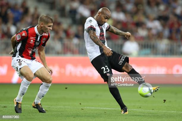Nice's French defender Maxime Le Marchand vies with Guingamp's French forward Jimmy Briand during the French L1 football match Nice vs Guingamp on...
