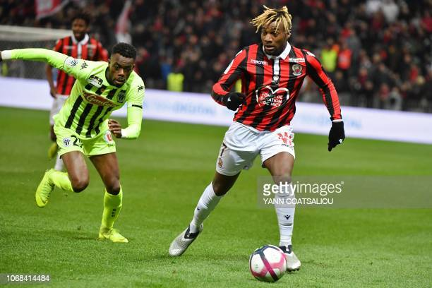 Nice's French forward Allan SaintMaximin is chased by Angers' Ivorian forward Thomas Toure during the French L1 football match OGC Nice vs Angers SCO...