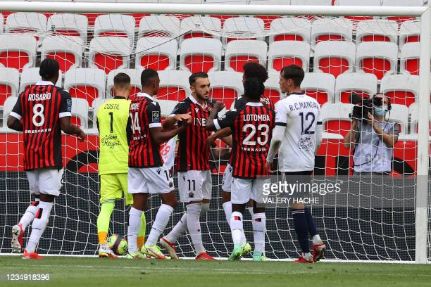 """Nice's French forward Amine Gouiri celebrates with teammates after he scored the third goal during the French L1 """"Huis clos"""" football match between..."""