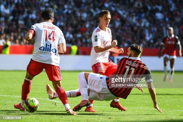 Nice's French forward Amine Gouiri fights for the ball with Lyon's French defender Leo Dubois and Lyon's French midfielder Maxence Caqueret during...