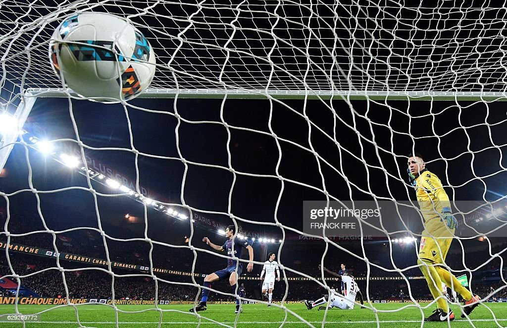 Nice's French goalkeeper Yoan Cardinale (R) eyes the ball entering the goal during the French L1 football match between Paris Saint-Germain (PSG) and Nice (OGCN) at the Parc des Princes stadium in Paris on December 11, 2016. / AFP / FRANCK
