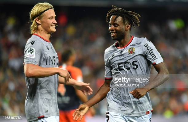 Nice's French midfielder Adrien Tameze Aousta is congratulated by his teammate Nice's Danish forward Kasper Dolberg after scoring during the French...