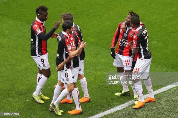 Nice's French midfielder Allan SaintMaximin celebrates with teammates Nice's Italian forward Mario Balotelli Nice's french midfielder Pierre...