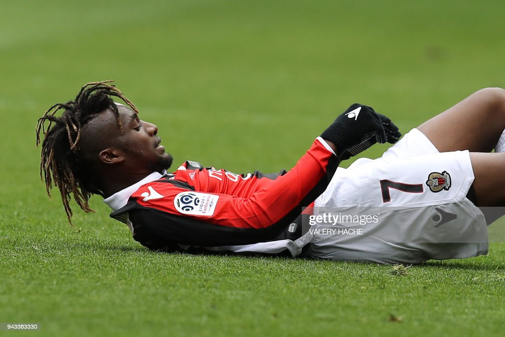 Nice's French midfielder Allan Saint-Maximin reacts on the ground during the French L1 football match Nice vs Rennes on april 8, 2018 at the 'Allianz Riviera' stadium in Nice, southeastern France. /