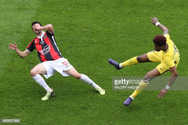 Nice's french midfielder Pierre LeesMelou and Paris SaintGermain's French defender Presnel Kimpembe collide during the French L1 football match Nice...