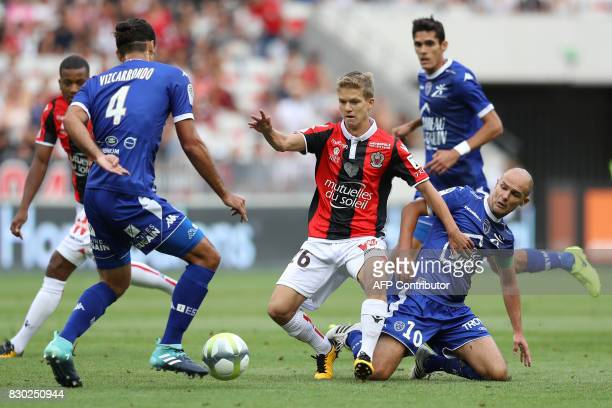 Nice's French midfielder Vincent Koziello vies with Troyes' French midfielder Benjamin Nivet and Troyes Oswaldo Vizcarrondo during the French L1...