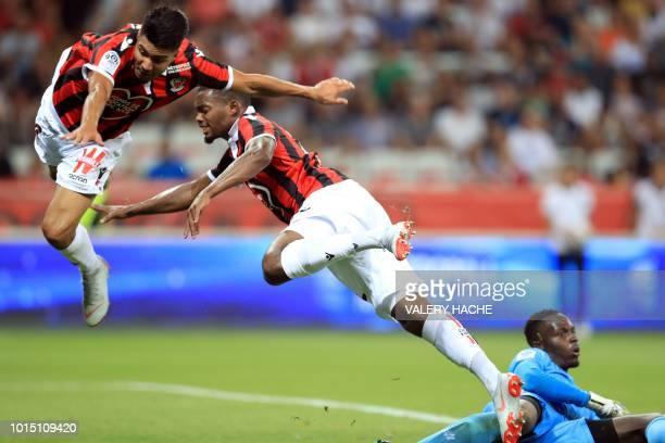 TOPSHOT Nice's French midfielder Wylan Cyprien and Nice's Tunisian forward Bassem Srarfi vie with Reims goalkeeper Ghislain Nclomande Konan during...