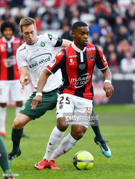 Nice's French midfielder Wylan Cyprien vies for the ball with SaintEtienne's Slovenian forward Robert Beric during the French L1 football match...