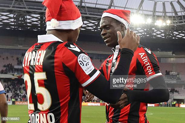 Nice's Italian forward Mario Balotelli and Nice's French midfielder Wylan Cyprien wearing Santa Claus bonnets celebrate at the end of the French L1...