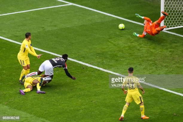 Nice's Italian forward Mario Balotelli fouls Paris SaintGermain's French defender Presnel Kimpembe as he heads the ball against the post of Paris...