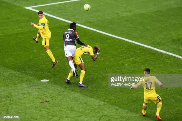 Nice's Italian forward Mario Balotelli fouls Paris SaintGermain's French defender Presnel Kimpembe as he heads the ball under the eye of Paris...