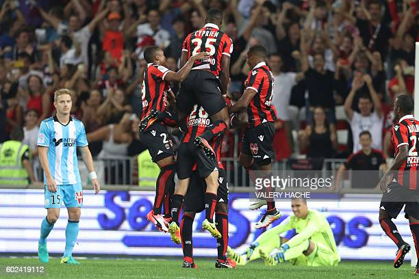 Nice's Italian forward Mario Balotelli is congratulated by teammates after scoring a goal during the French L1 football match OGC Nice vs Olympique...