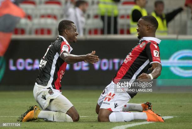 Nice's Ivorian midfielder Jean Michael Seri is congratulated by Nice's French midfielder Wylan Cyprien after scoring during the French L1 football...