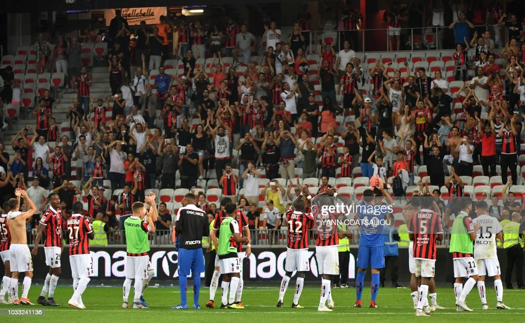 Nice's players salute their supporters as they celebrate after their victory following the French L1 football match between Nice and Rennes at The 'Allianz Riviera' Stadium in Nice, southern France on September 14, 2018.
