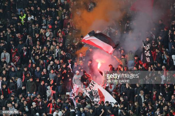 Nice's supporters light a flare during the French L1 football match Nice vs Paris SaintGermain on March 18 2018 at the Allianz Riviera stadium in...
