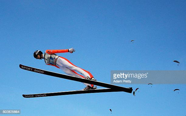 Nicholas Alexander of the USA soars through the air with paragliders during his practice jump on Day 2 of the 64th Four Hills Tournament on December...