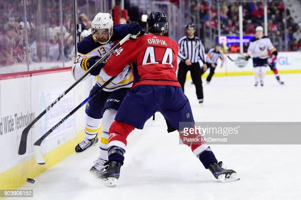 Nicholas Baptiste of the Buffalo Sabres and Brooks Orpik of the Washington Capitals battle for the puck in the second period at Capital One Arena on...