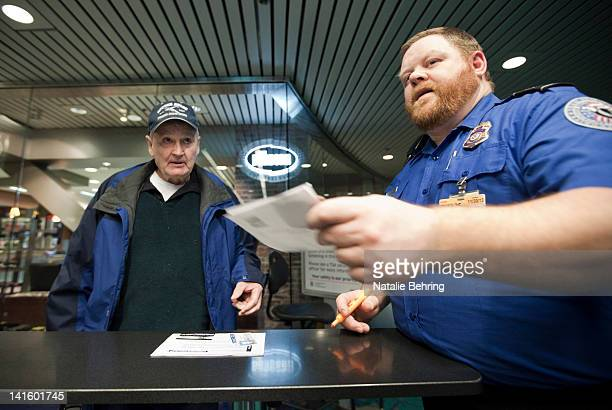 Nicholas Barker of Council Idaho is helped by a Transportation Security Administration officer on a special lane for elderly passengers to receive a...