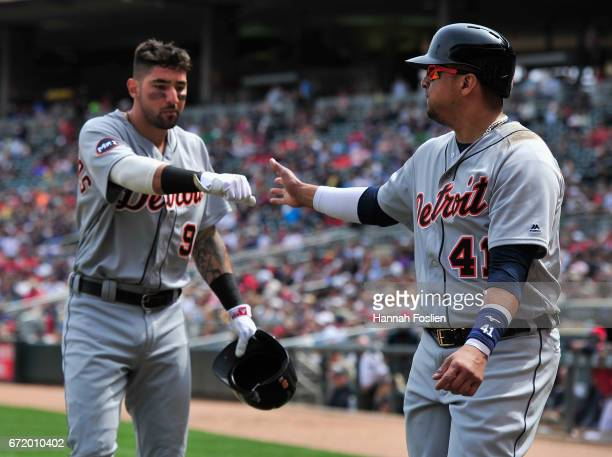 Nicholas Castellanos and Victor Martinez of the Detroit Tigers celebrate scoring runs against the Minnesota Twins during the third inning of the game...