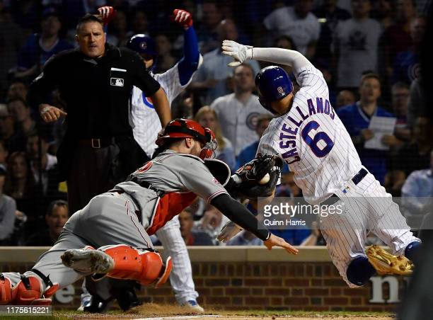 Nicholas Castellanos of the Chicago Cubs beats the tag from Curt Casali of the Cincinnati Reds to score in the fourth inning at Wrigley Field on...