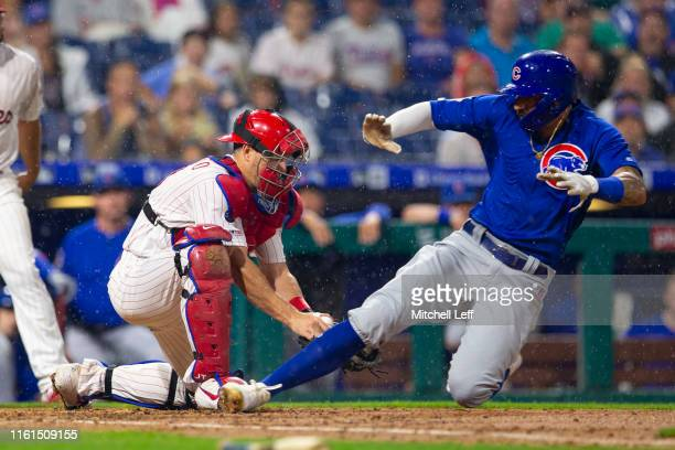 Nicholas Castellanos of the Chicago Cubs slides past JT Realmuto of the Philadelphia Phillies to score a run in the top of the fourth inning at...