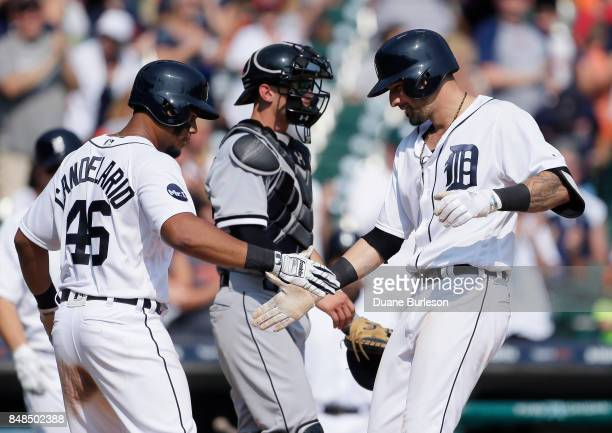 Nicholas Castellanos of the Detroit Tigers celebrates with Jeimer Candelario of the Detroit Tigers as he crosses the plate in front of catcher Rob...