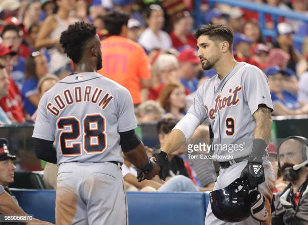 Nicholas Castellanos of the Detroit Tigers is congratulated by Niko Goodrum after hitting a grand slam home run in the fifth inning during MLB game...