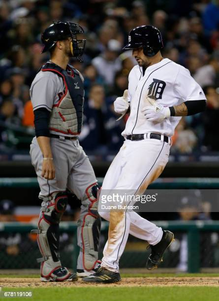 Nicholas Castellanos of the Detroit Tigers scores past catcher Yan Gomes of the Cleveland Indians on a sacrifice fly hit by Victor Martinez of the...