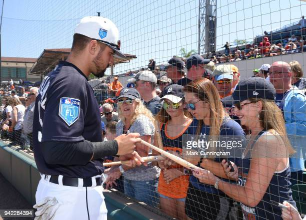 Nicholas Castellanos of the Detroit Tigers signs autographs for fans through the new protective netting prior to the Spring Training game against the...