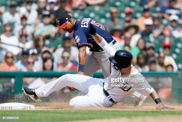 Nicholas Castellanos of the Detroit Tigers slides into third base beating the tag from Eduardo Escobar of the Minnesota Twins during the ninth inning...
