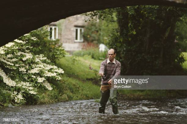 Nicholas Edwards, Baron Crickhowell, fly fishing for trout on a tributary of the River Usk from the rear of his home in the town of Crickhowell,...