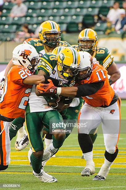 Nicholas Edwards of the Edmonton Eskimos gets stopped by Keynan Parker and Korey Jones of the BC Lions during a CFL game at Commonwealth Stadium on...