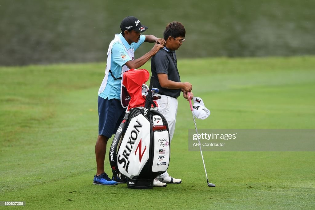 Nicholas Fung of Malaysia (R) receives a shoulder massage by his caddie on the fairway during the second round of the 2017 CIMB Classic golf tournament in Kuala Lumpur on October 13, 2017. /